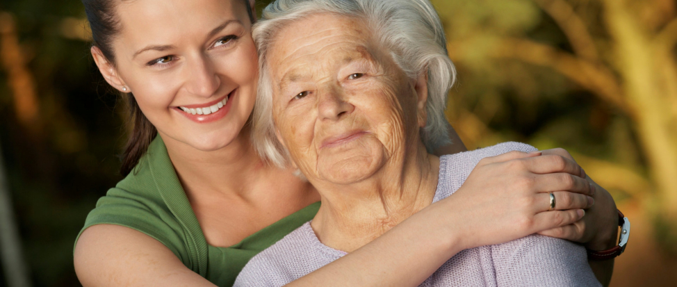 A caregiver hugging an elderly