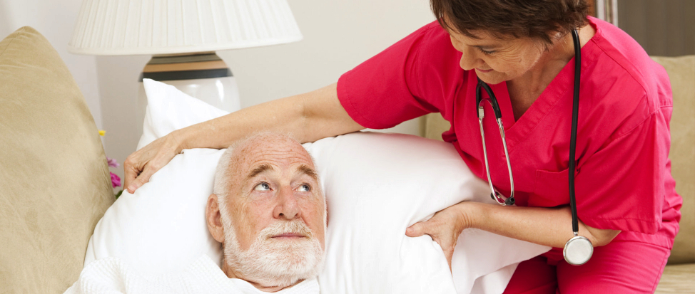 A nurse fixing the pillow used by the elderly