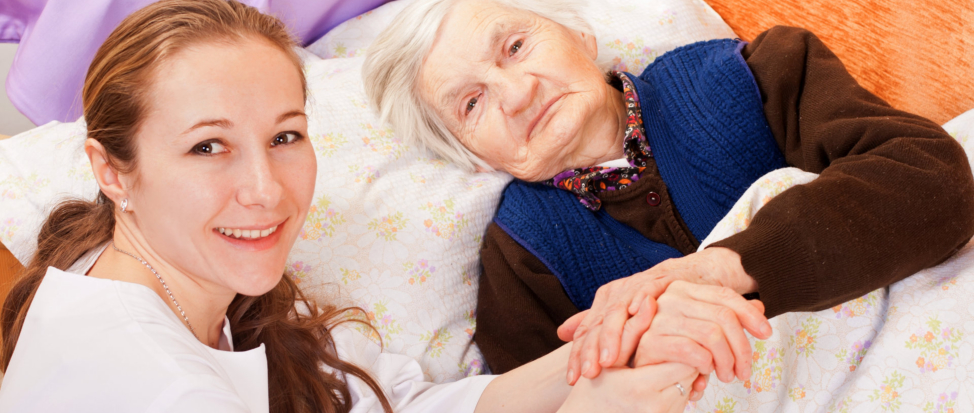A caregiver holding the hands of an elderly
