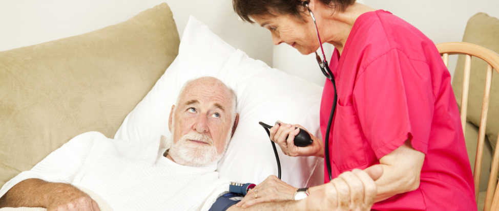 A nurse checking the blood pressure of an elderly
